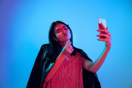 Beautiful female half-length portrait isolated on blue studio background in neon light. Young emotional woman. Human emotions, facial expression concept. Making selfie or content for her vlog. Stockfoto