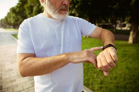 Senior man as runner with fitness tracker at the citys street. Caucasian male model using gadgets while jogging and cardio training in summers morning. Healthy lifestyle, sport, activity concept. Stock Photo