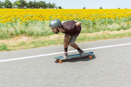 Skateboarder doing a trick at the citys street in sunny day. Young man in equipment riding and longboarding in action. Concept of leisure activity, sport, extreme, hobby and motion. As fast as a car.