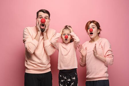 Portrait of young family celebrating red nose day. Male and female models looks crazy happy, astonished, surprised on coral studio background. Victory, delight concept. Human facial emotions. Stock Photo