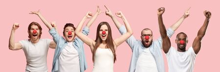 Collage of happy caucasian and african-american people as a clowns celebrating red nose day. Male and female models on coral studio background. Victory, delight concept. Human facial emotions.