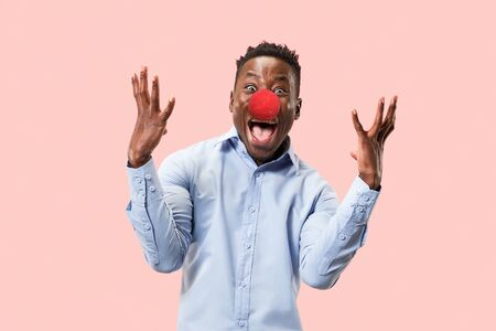 Portrait of young happy man celebrating red nose day. African male model looks astonished on pink studio background. Victory, delight concept. Human facial emotions, expression concept. Trendy colors.