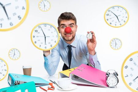 Young office worker celebrating red nose day. Male model holding the clock and waiting five minutes before the end. Concept of office workers troubles, business, problems or holidays.