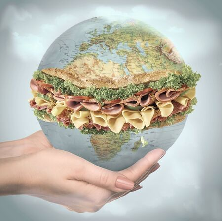 We are that we eat everyday. People of the Earth advocate for preservation of healthy food on the planet. Save the taste of nature for saving the youth. Female hands holding a globe as a sandwich.