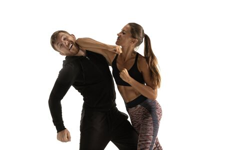 Man in black outfit and athletic caucasian woman fighting on white studio background. Womens self-defense, rights, equality concept. Confronting domestic violence or robbery on the street. Reklamní fotografie - 127951237