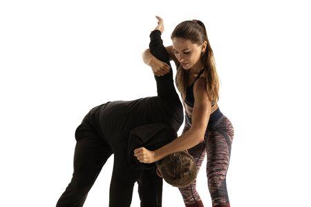 Homme en tenue noire et femme caucasienne athlétique combats sur fond de studio blanc. Autodéfense des femmes, droits, concept d'égalité. Faire face à la violence domestique ou au vol dans la rue. Banque d'images
