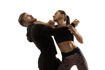 Uomo in abito nero e atletica donna caucasica che combattono su sfondo bianco studio. Autodifesa delle donne, diritti, concetto di uguaglianza. Affrontare la violenza domestica o la rapina per strada. Archivio Fotografico