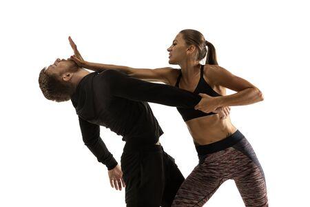 Hombre en traje negro y atlética mujer caucásica peleando sobre fondo blanco de estudio. Autodefensa de las mujeres, derechos, concepto de igualdad. Enfrentar la violencia doméstica o el robo en la calle. Foto de archivo
