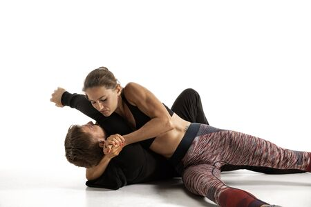 Man in black outfit and athletic caucasian woman fighting on white studio background. Womens self-defense, rights, equality concept. Confronting domestic violence or robbery on the street.