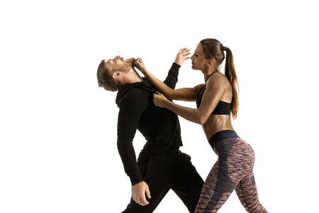 Mann im schwarzen Outfit und athletische kaukasische Frau, die auf weißem Studiohintergrund kämpfen. Selbstverteidigung der Frauen, Rechte, Gleichstellungskonzept. Konfrontation mit häuslicher Gewalt oder Raub auf der Straße. Standard-Bild