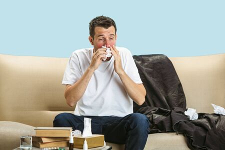 Young man suffering from hausehold dust or seasonal allergy. Sneezing in the napkin and sitting surrounded by used napkins on the floor and sofa. Taking medicines with no result. Healthcare concept. Stock Photo