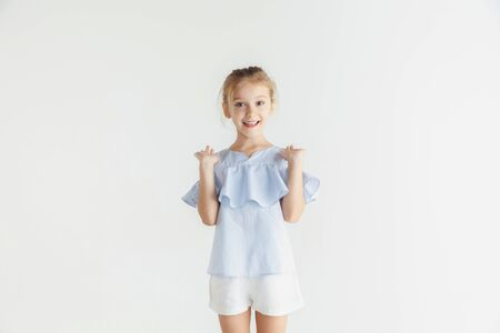 Stylish little smiling girl posing in casual clothes isolated on white studio background. Caucasian blonde female model. Human emotions, facial expression, childhood. Showing, inviting or greeting.
