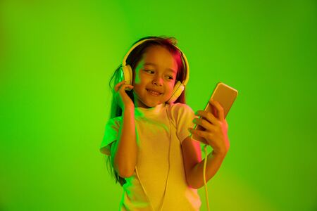 Beautiful female half-length portrait isolated on green backgroud in neon light. Young emotional girl. Human emotions, facial expression concept. Using smartphone for vlog, selfie, chating, gaming. Stockfoto
