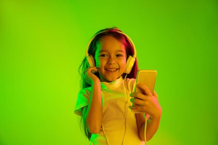 Beautiful female half-length portrait isolated on green backgroud in neon light. Young emotional girl. Human emotions, facial expression concept. Using smartphone for vlog, selfie, chating, gaming.