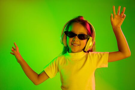 Beautiful female half-length portrait isolated on green backgroud in neon light. Young emotional teen girl in sunglasses. Human emotions, facial expression concept. Trendy colors. Dancing, smiling. Standard-Bild