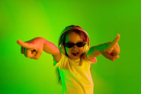 Beautiful female half-length portrait isolated on green backgroud in neon light. Young emotional teen girl in sunglasses. Human emotions, facial expression concept. Trendy colors. Dancing, smiling.