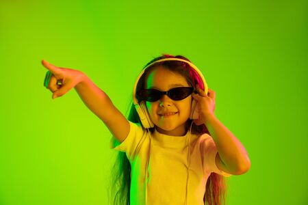 Beautiful female half-length portrait isolated on green backgroud in neon light. Young emotional teen girl. Human emotions, facial expression concept. Dancing in sunglasses and pointing up.
