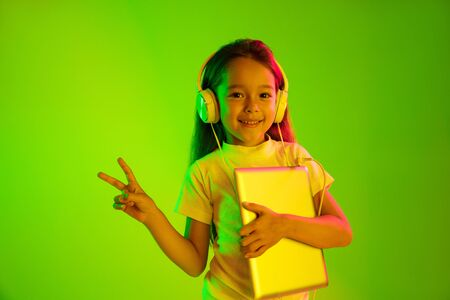 Beautiful female half-length portrait isolated on green backgroud in neon light. Young emotional teen girl. Human emotions, facial expression concept. Trendy colors. Holding tablet and smiling.