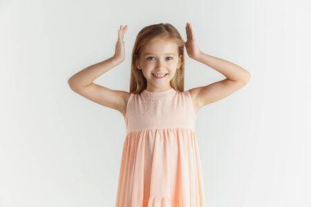 Elegante niña sonriente posando en vestido aislado sobre fondo blanco de estudio. Modelo de mujer rubia caucásica. Las emociones humanas, la expresión facial, la infancia. Sonriendo, bailando con las manos cerca de la cabeza.
