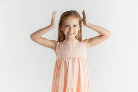 Stylish little smiling girl posing in dress isolated on white studio background. Caucasian blonde female model. Human emotions, facial expression, childhood. Smiling, dancing with hands near head.