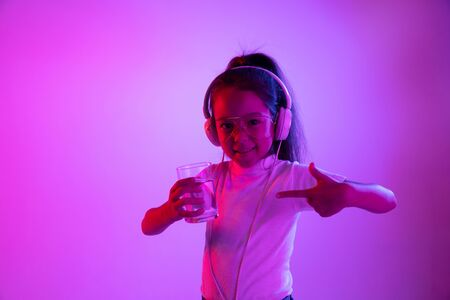 Beautiful female half-length portrait isolated on purple backgroud in neon light. Young emotional teen girl in sunglasses. Human emotions, facial expression concept. Pointing on glass of water.