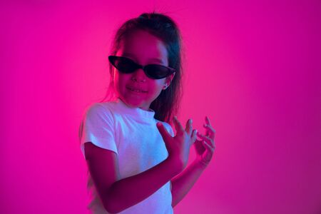 Beautiful female half-length portrait isolated on purple backgroud in neon light. Young emotional teen girl in sunglasses. Human emotions, facial expression concept. Trendy colors. Dancing, smiling.