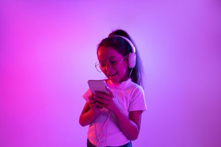 Beautiful female half-length portrait isolated on purple backgroud in neon light. Emotional girl in eyeglasses. Human emotions, facial expression concept. Listening to music, making selfie, gaming.
