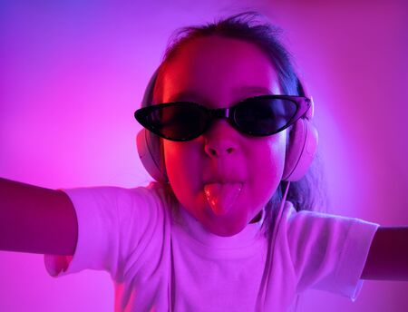 Beautiful female half-length portrait isolated on purple backgroud in neon light. Young emotional girl in sunglasses. Human emotions, facial expression concept. Trendy colors. Dancing, crazy gremaces.