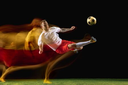 Catching. Young caucasian male football or soccer player in sportwear and boots kicking ball for the goal in mixed light on dark background. Concept of healthy lifestyle, professional sport, hobby.