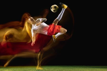 Overcoming. Young caucasian male football or soccer player in sportwear and boots kicking ball for the goal in mixed light on dark background. Concept of healthy lifestyle, professional sport, hobby.