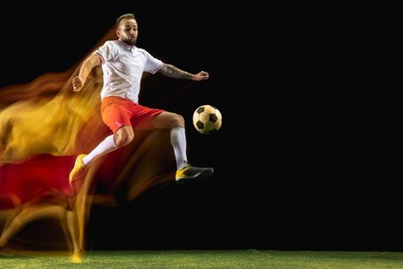 Self-build. Young caucasian male football or soccer player in sportwear and boots kicking ball for the goal in mixed light on dark background. Concept of healthy lifestyle, professional sport, hobby.