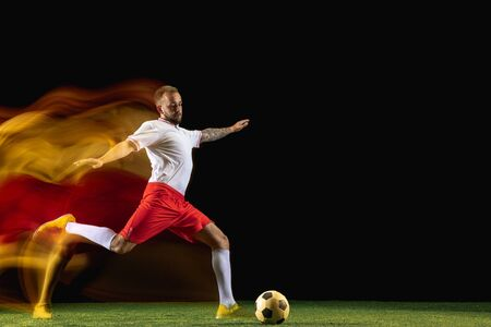 Winner. Young caucasian male football or soccer player in sportwear and boots kicking ball for the goal in mixed light on dark background. Concept of healthy lifestyle, professional sport, hobby.