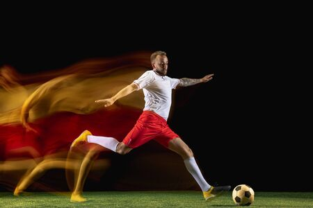 One step. Young caucasian male football or soccer player in sportwear and boots kicking ball for the goal in mixed light on dark background. Concept of healthy lifestyle, professional sport, hobby.