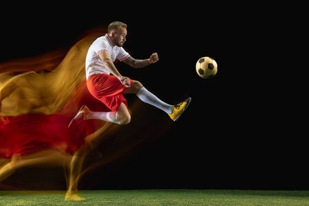 Flight. Young caucasian male football or soccer player in sportwear and boots kicking ball for the goal in mixed light on dark background. Concept of healthy lifestyle, professional sport, hobby. Imagens