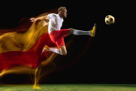 Flying. Young caucasian male football or soccer player in sportwear and boots kicking ball for the goal in mixed light on dark background. Concept of healthy lifestyle, professional sport, hobby.