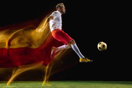 Higher. Young caucasian male football or soccer player in sportwear and boots kicking ball for the goal in mixed light on dark background. Concept of healthy lifestyle, professional sport, hobby.