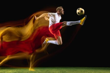 Jump. Young caucasian male football or soccer player in sportwear and boots kicking ball for the goal in mixed light on dark background. Concept of healthy lifestyle, professional sport, hobby.