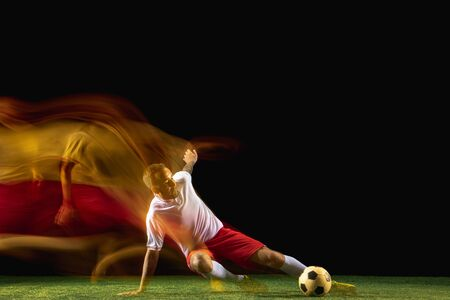 Flexible. Young caucasian male football or soccer player in sportwear and boots kicking ball for the goal in mixed light on dark background. Concept of healthy lifestyle, professional sport, hobby.