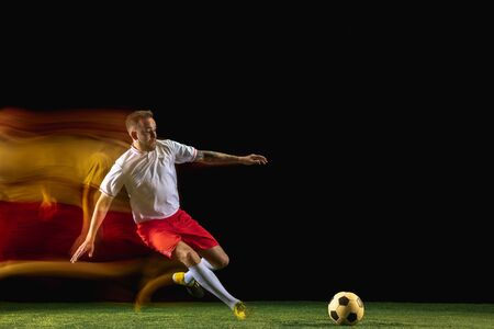 Run. Young caucasian male football or soccer player in sportwear and boots kicking ball for the goal in mixed light on dark background. Concept of healthy lifestyle, professional sport, hobby.