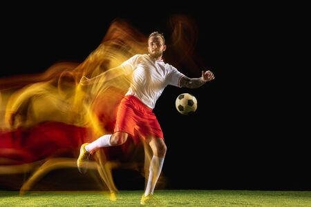 In fire. Young caucasian male football or soccer player in sportwear and boots kicking ball for the goal in mixed light on dark background. Concept of healthy lifestyle, professional sport, hobby.