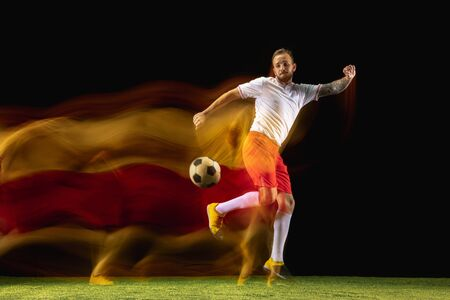 Burn. Young caucasian male football or soccer player in sportwear and boots kicking ball for the goal in mixed light on dark background. Concept of healthy lifestyle, professional sport, hobby.
