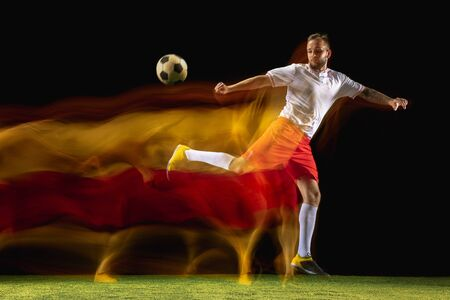 Burning. Young caucasian male football or soccer player in sportwear and boots kicking ball for the goal in mixed light on dark background. Concept of healthy lifestyle, professional sport, hobby.