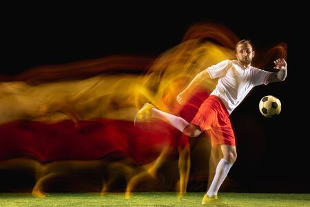 Speed. Young caucasian male football or soccer player in sportwear and boots kicking ball for the goal in mixed light on dark background. Concept of healthy lifestyle, professional sport, hobby. Imagens