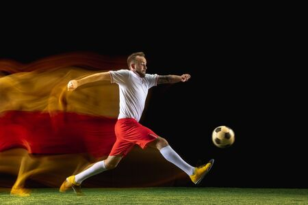 First. Young caucasian male football or soccer player in sportwear and boots kicking ball for the goal in mixed light on dark background. Concept of healthy lifestyle, professional sport, hobby.