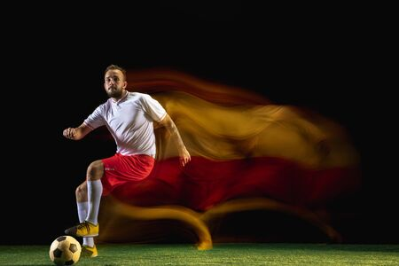 Emotions. Young caucasian male football or soccer player in sportwear and boots kicking ball for the goal in mixed light on dark background. Concept of healthy lifestyle, professional sport, hobby. Imagens