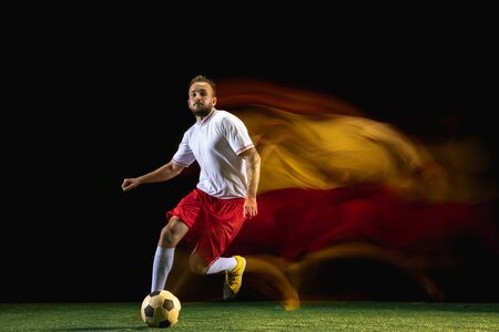 Propose. Young caucasian male football or soccer player in sportwear and boots kicking ball for the goal in mixed light on dark background. Concept of healthy lifestyle, professional sport, hobby.