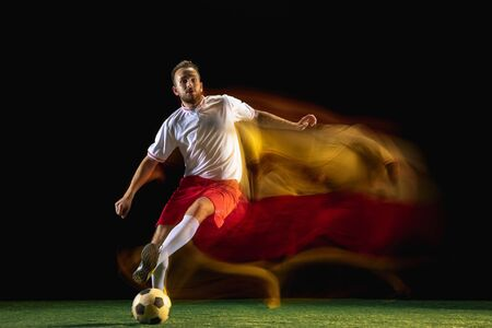 Target. Young caucasian male football or soccer player in sportwear and boots kicking ball for the goal in mixed light on dark background. Concept of healthy lifestyle, professional sport, hobby. Imagens
