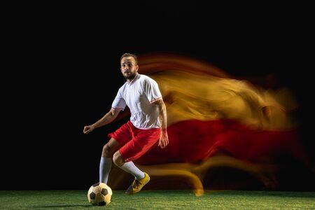 Team. Young caucasian male football or soccer player in sportwear and boots kicking ball for the goal in mixed light on dark background. Concept of healthy lifestyle, professional sport, hobby.