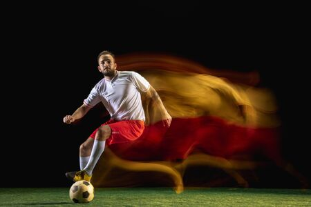 Strategy. Young caucasian male football or soccer player in sportwear and boots kicking ball for the goal in mixed light on dark background. Concept of healthy lifestyle, professional sport, hobby.