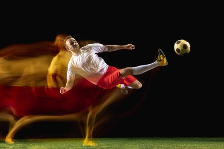 Moment. Young caucasian male football or soccer player in sportwear and boots kicking ball for the goal in mixed light on dark background. Concept of healthy lifestyle, professional sport, hobby.